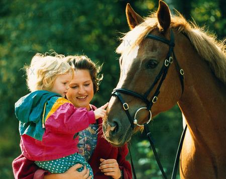 kvinna barn och häst